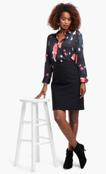 Load image into Gallery viewer, Full body front view of a woman wearing a black, blue & pink abstract printed kaleidoscope blouse from Nic + Zoe tucked in to a high-waisted skirt