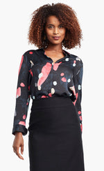 Load image into Gallery viewer, Front view of a woman wearing a black, blue & pink abstract printed kaleidoscope blouse from Nic + Zoe tucked in to a high-waisted skirt