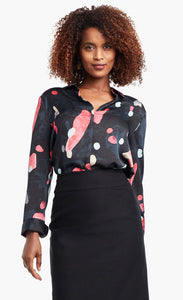 Front view of a woman wearing a black, blue & pink abstract printed kaleidoscope blouse from Nic + Zoe tucked in to a high-waisted skirt