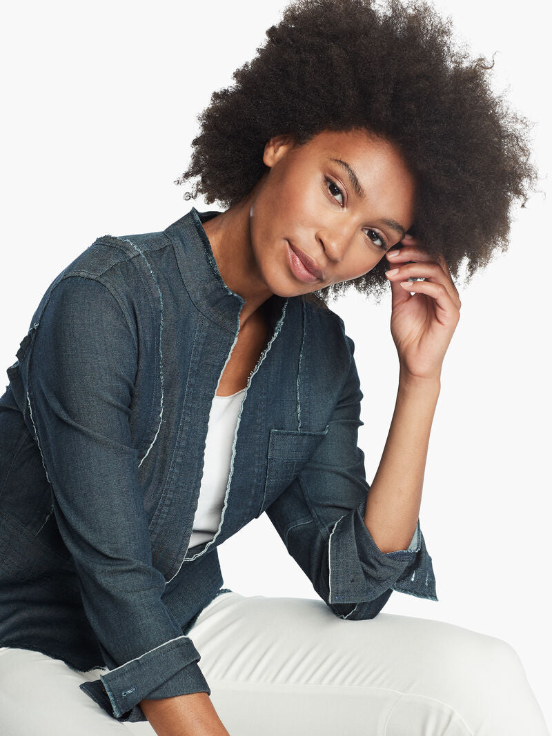 Front, top half view of a woman sitting leaned forward wearing white pants and the Nic + Zoe Favorite Denim Jacket. The dark denim jacket features frayed stitching, long sleeves that can be cuffed, and a short stand collar.