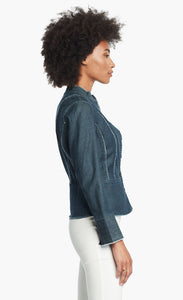 Side, top half view of a woman wearing white pants and the Nic + Zoe Favorite Denim Jacket. The dark denim jacket features frayed stitching, a cropped cut, and a short stand collar.