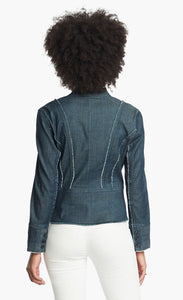 Back, top half view of a woman wearing white pants and the Nic + Zoe Favorite Denim Jacket. The dark denim jacket features frayed stiching, a cropped cut, and a short stand collar.