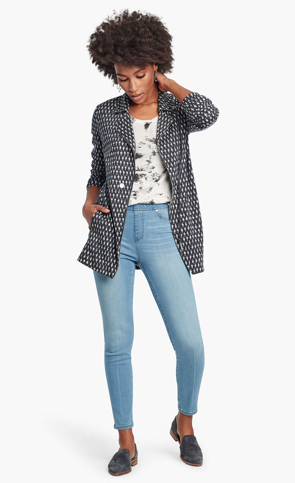 Front, full body view of a woman wearing the Nic + Zoe Ponte Ikat Jacket over a white printed top and with fitted jeans. The jacket is indigo with a white speck print all over it. It has a flat, notched lapel, and a front, off-center zipper.