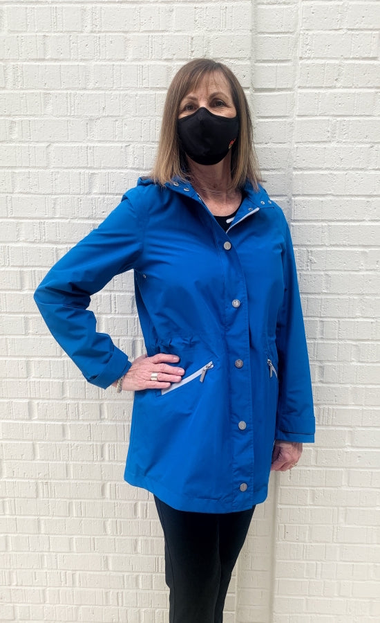 Front top half view of a woman wearing the nikki jones royal blue magic print rain jacket. This jacket has a zipper and button up front, front diagonal zipped pockets, and cuffed sleeves.