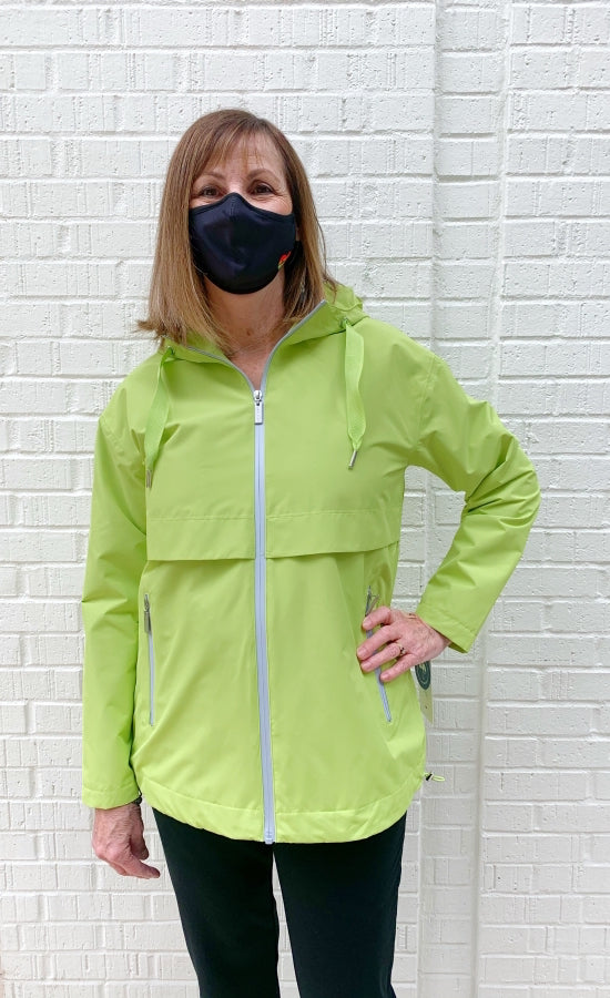 Front top half view of woman wearing the nikki jones magic print lime rain jacket. This jacket has a zipper front with two front zipper pockets, front venting over the chest and an adjustable hood and hem.