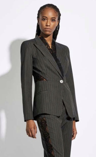 Front top half view of a woman wearing the Oblique Creations Striped Jacket. This jacket is black with white stripes. It has a single front button, long sleeves, and detailed see through mesh on the sides of the waist and as trim added to the lapels.