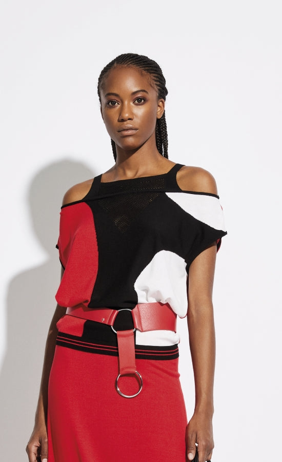Front, top half view of a woman wearing the Oblique Creations Cold Shoulder Top. This cold shoulder top is black, red, and white, with connected short sleeves. The neck has a cutout mesh-like v-neck. On top of the top is a red belt near the waist.