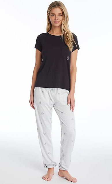 Front full body view of a woman wearing the PJ Salvage Lily Rose Tee and Pj Salvage Lily Rose Banded Pant. The short sleeve t-shirt is black and has a single front pocket on the left side with a tiny white french bulldog face printed on it. The banded pant is a heathered light grey with matching tiny french bulldog faces printed on it in black