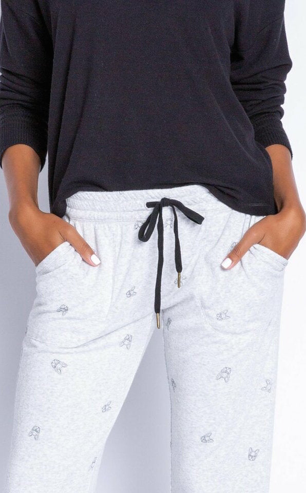 Close up view of a woman wearing the Lily Rose Banded Pant. The pant is a heathered light grey and has a black tie waistband and black tiny french bulldog faces printed all over it.