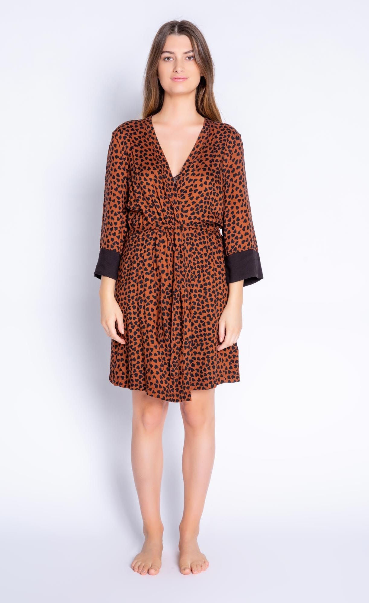 Front full body view of woman wearing the PJ Salvage Wild Love Robe. This short, mocha/brown colored robe has a heart shaped animal print all over it, contrasting black sleeves, and a belt at the waist.