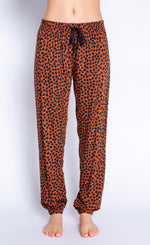 Load image into Gallery viewer, Front view of the bottom half of a woman wearing the PJ Salvage Wild Love Banded Pant. This banded pant is mocha/brown colored with a black heart shaped animal print. It has a black tie waistband.