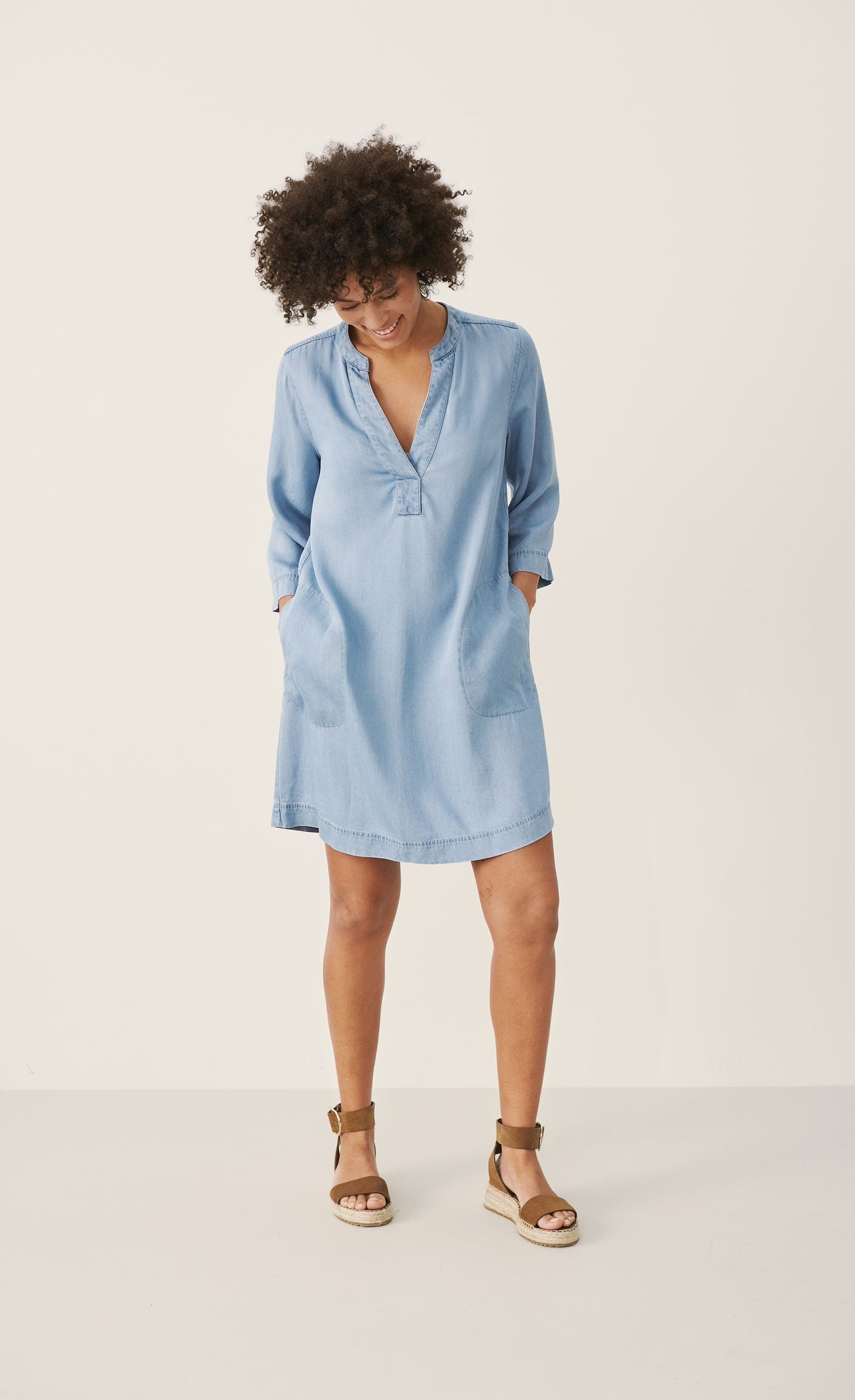 Front full body view of a woman wearing the part two ingeline dress. This dress is a light blue denim. It ends at the knees, has 3/4 length sleeves, and a v-neck.