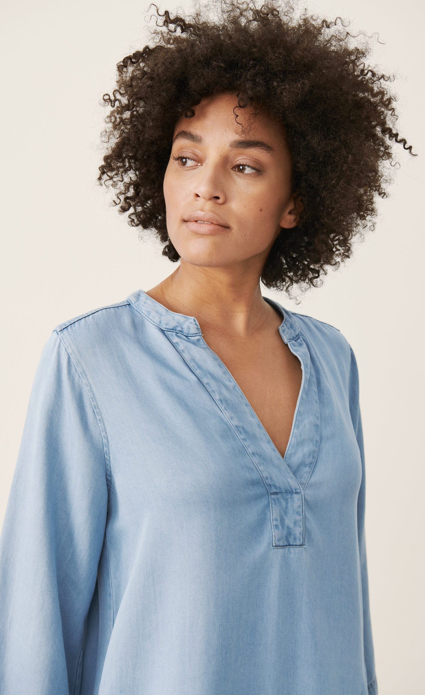 Front top half view of a woman wearing the part two ingeline dress. This dress is a light blue denim. It has 3/4 length sleeves and a v-neck.