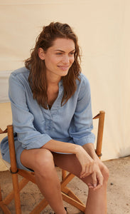 Front view of a woman sitting in a a chair and wearing the part two ingeline dress. This dress is a light blue denim. It has 3/4 length sleeves and a v-neck.