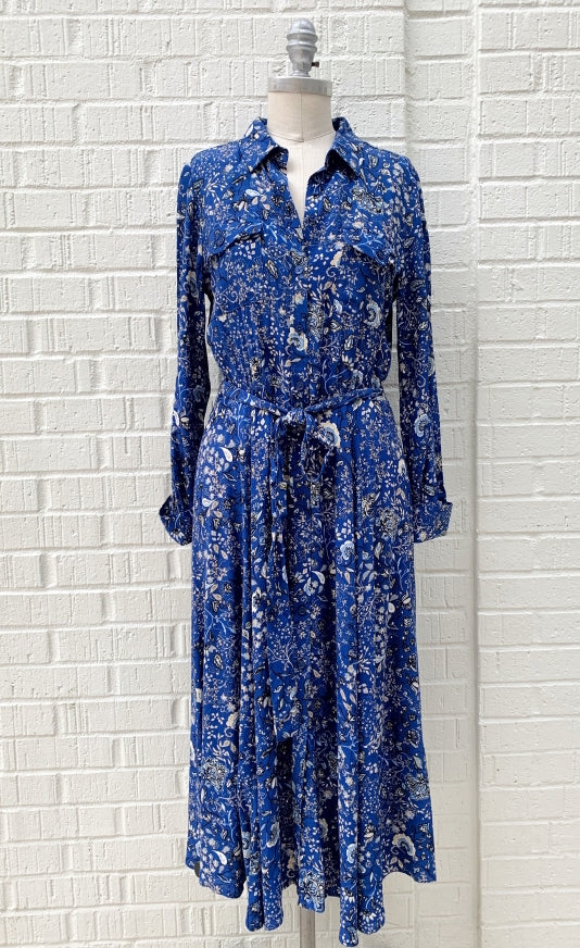 front full body view of a mannequin wearing the part two true paisley flower dress. This dress is ultramarine/vibrant blue color with white paisley floral print. The dress sits below the knees and has a button down front and tie belt.