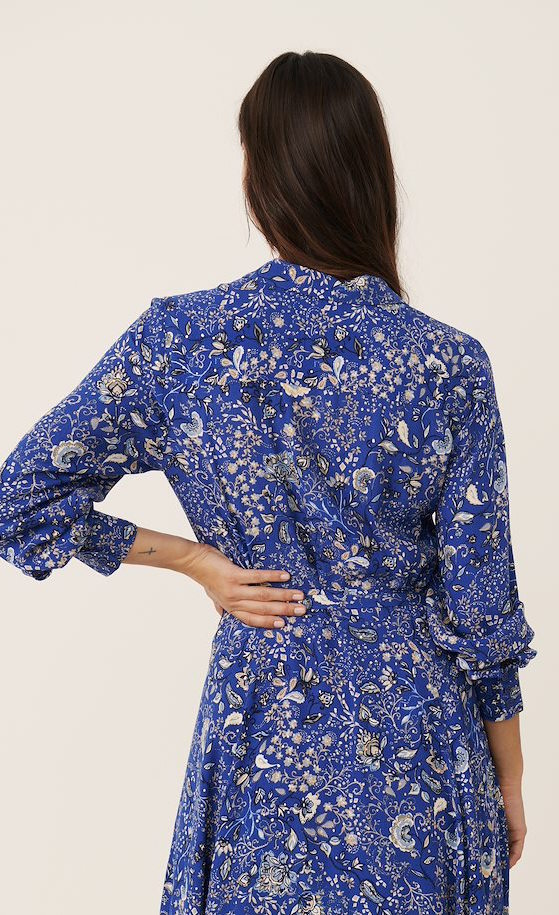 Back full body view of a woman wearing the part two true paisley flower dress. This dress is ultramarine/vibrant blue color with white paisley floral print. The dress has a tie belt at the waist.