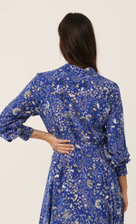 Load image into Gallery viewer, Back full body view of a woman wearing the part two true paisley flower dress. This dress is ultramarine/vibrant blue color with white paisley floral print. The dress has a tie belt at the waist.