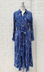 Load image into Gallery viewer, front full body view of a mannequin wearing the part two true paisley flower dress. This dress is ultramarine/vibrant blue color with white paisley floral print. The dress sits below the knees and has a button down front and tie belt.