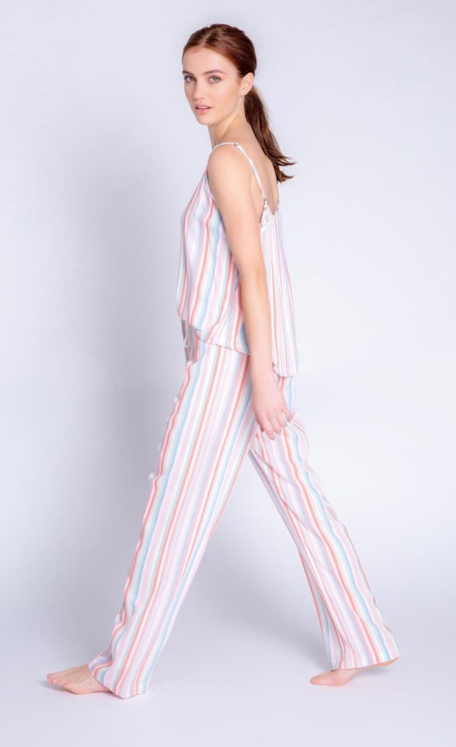 Left side full body view of a woman wearing the saturday morning stripe set. This set includes the saturday morning stripe tank and the saturday morning stripe pant. This pj set is multicolored striped.