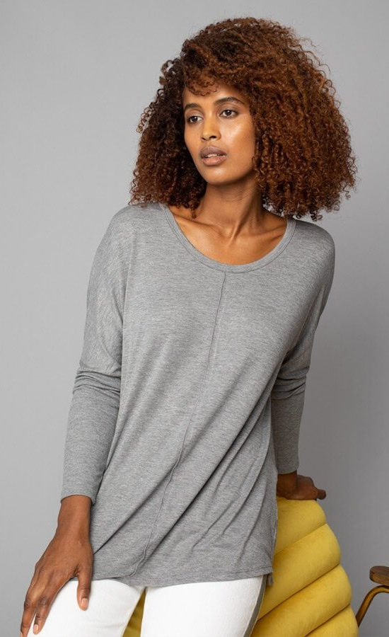 Front, top half view of a woman wearing the grey Lola & Sophie scoop neck shirttail tee. This shirt has a boxy silhouette, indent detailing around the neck and down the front, and fitted sleeves.