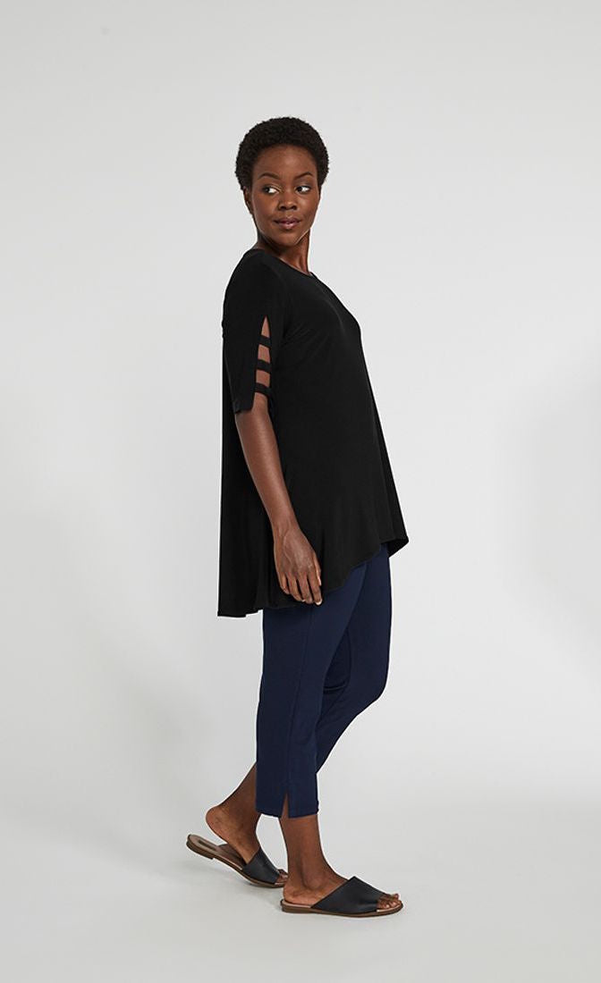 Left side full body view of a woman wearing blue pants and the sympli capture tunic in black. This top has short sleeves with striped slits, a round neck, and an arched high-low hem.
