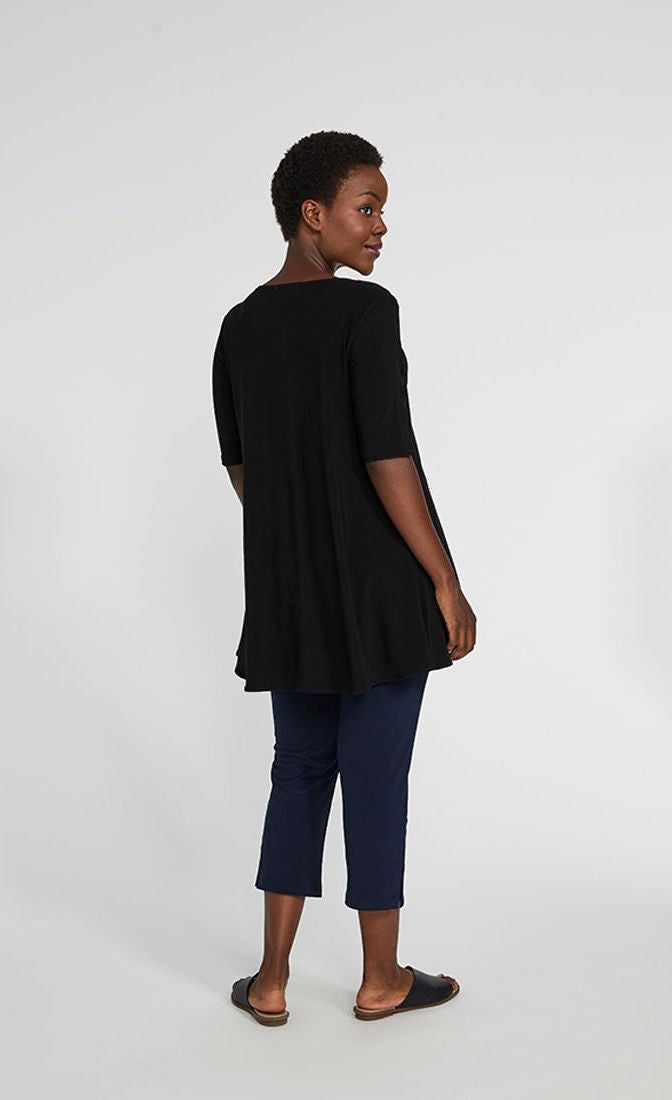 Back full body view of a woman wearing blue pants and the sympli capture tunic in black. This top has short sleeves with striped slits and an arched high-low hem.