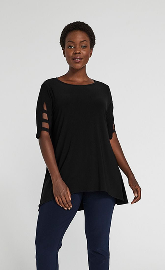 Front top half view of a woman wearing blue pants and the sympli capture tunic in black. This top has short sleeves with striped slits, a round neck, and an arched hem.