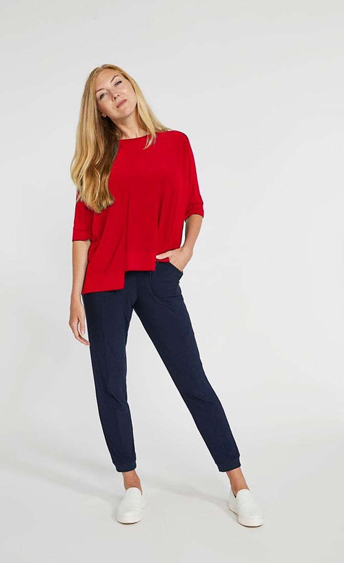 Front top full body view of a woman wearing the sympli motion boxy top in the color poppy with blue bottoms. The top has 3/4 length sleeves, a boat neck, and an asymmetrical double side-stepped hem.