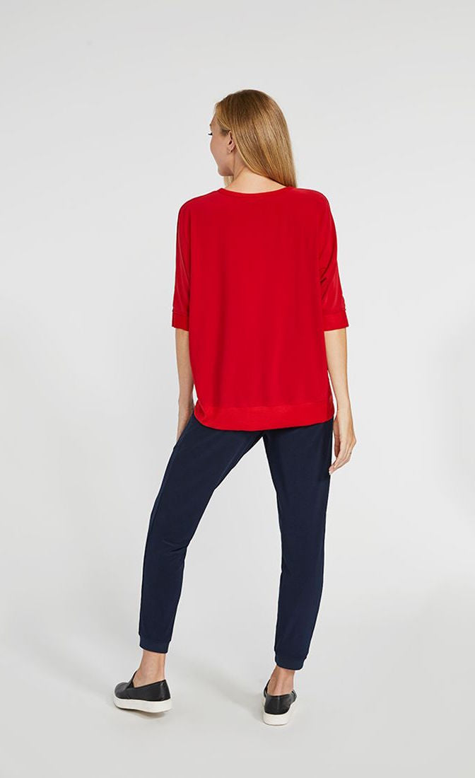 Back full body view of a woman wearing the sympli motion boxy top in the color poppy with blue bottoms. The top has 3/4 length sleeves and the back hem sits below the hips.