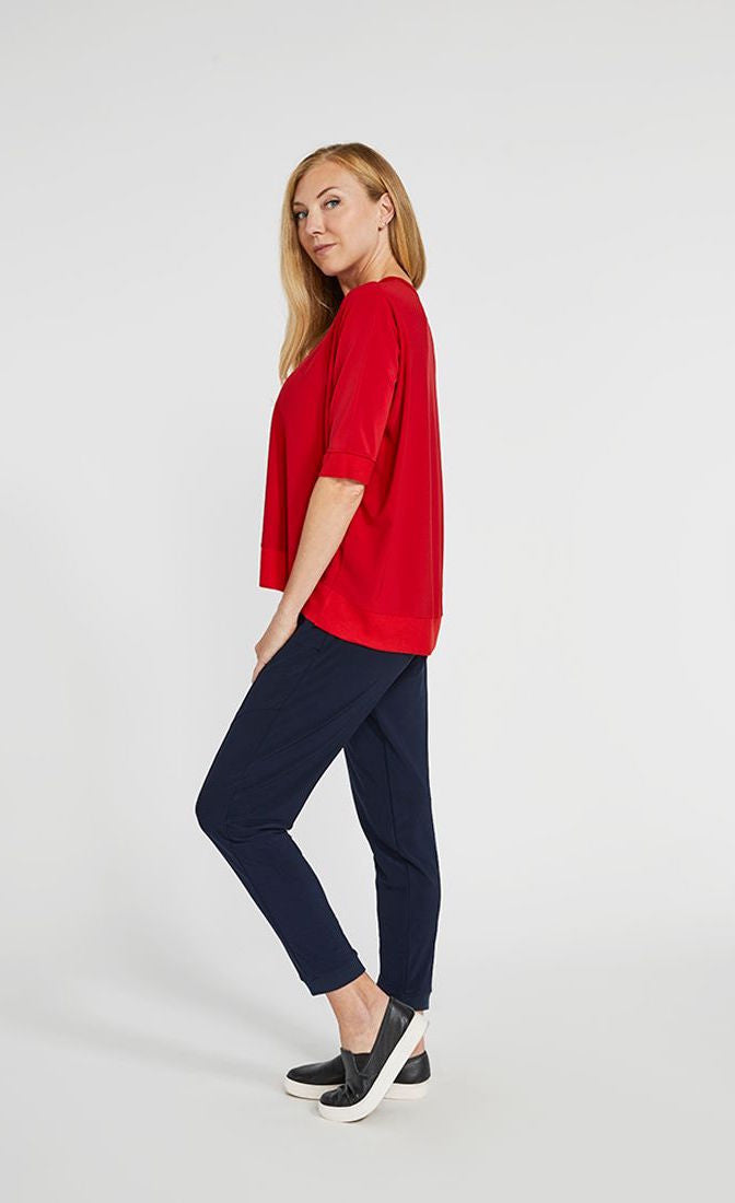 left side full body view of a woman wearing the sympli motion boxy top in the color poppy with blue bottoms. The top has 3/4 length sleeves and an asymmetrical double side-stepped hem.