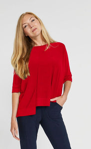 Front top half view of a woman wearing the sympli motion boxy top in the color poppy with blue bottoms. The top has 3/4 length sleeves, a boat neck, and an asymmetrical double side-stepped hem.