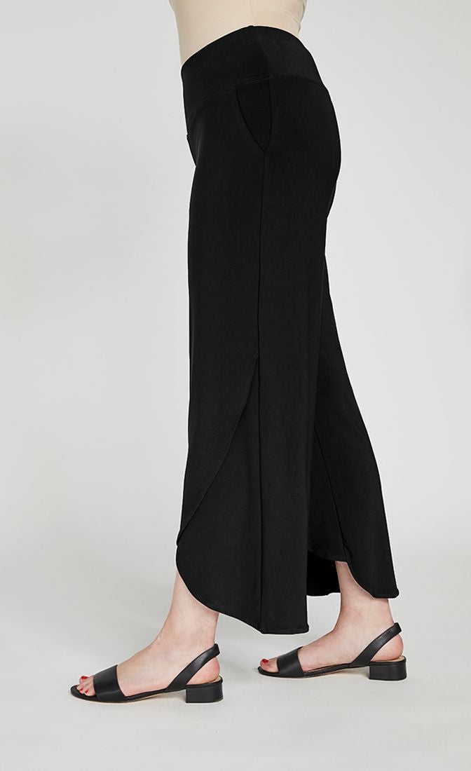 Left side bottom half view of a woman wearing the sympli narrow rapt pant. These pants are black and feature side pockets, a wide waistband, a wrapped look near the hem, and a relaxed, straight silhouette