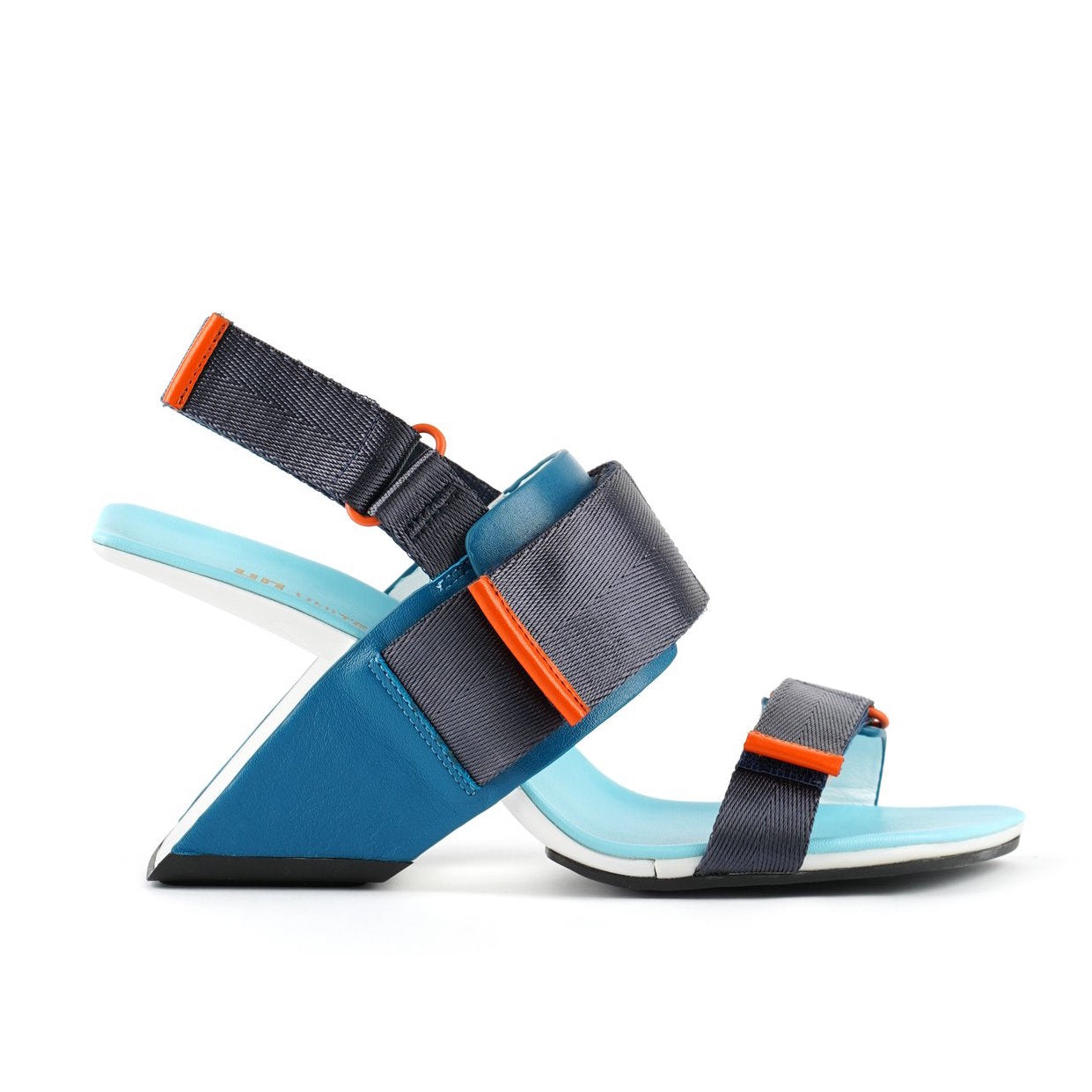 Outer view of the united nude loop run high heel sandal. This sandal is blue with a black back strap, a black strap over the instep, and a black strap over the toes.
