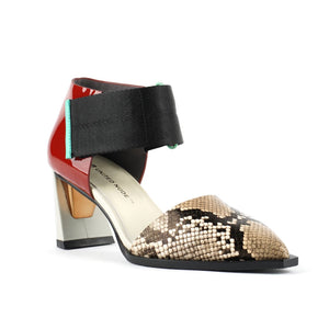 Outer front view of the united nude vita dorsey mid viper. This sandal has a pointed toe in snake skin and a red patent leather covered with a wide nylon adjustable strap around the front of the ankle. This sandal has a mid-heel with a gold and silver accent.