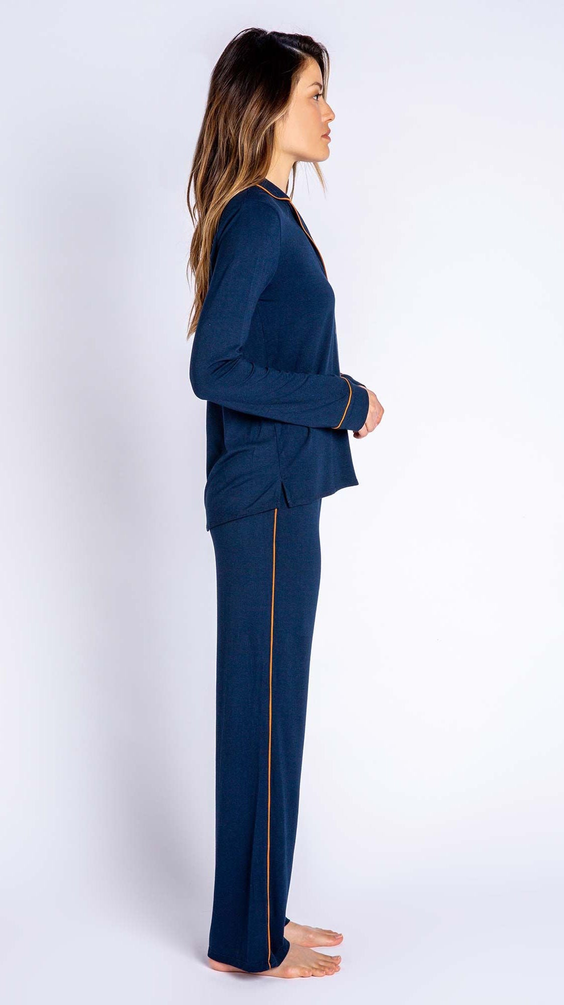 Side profile of woman wearing matching navy pj top and pj bottom set from PJ Salvage