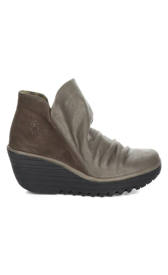 Outer side view of two toned wedge Yip Boot from Fly London. The front portion of the boot is a slouchy metallic grey leather while the back is a brown suede leather.