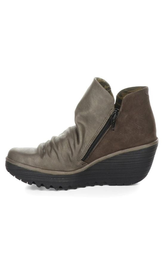 Inner side view of two toned wedge Yip Boot from Fly London with an inner zipper. The front portion of the boot is a slouchy metallic grey leather while the back is a brown suede leather.