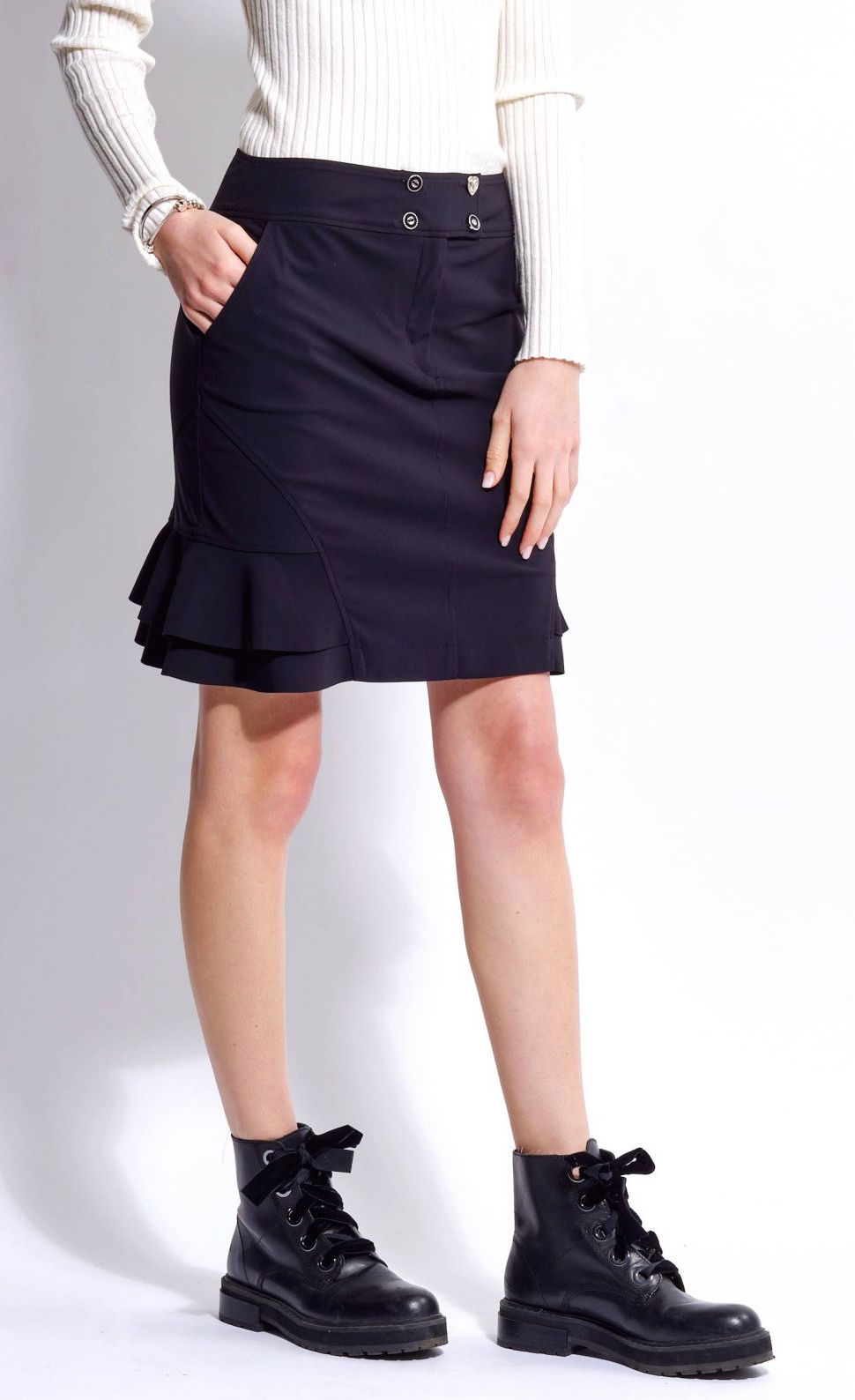 Right-sided front view of the bottom half of a woman wearing the mid-length indies cosmic black trumpet skirt with her hand in the side pocket and side ruffles showing at the bottom.