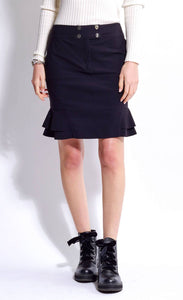 Front view of the bottom half of a woman wearing the mid-length indies cosmic black trumpet skirt with side ruffles at the bottom and a front zipper with a two-button closure.