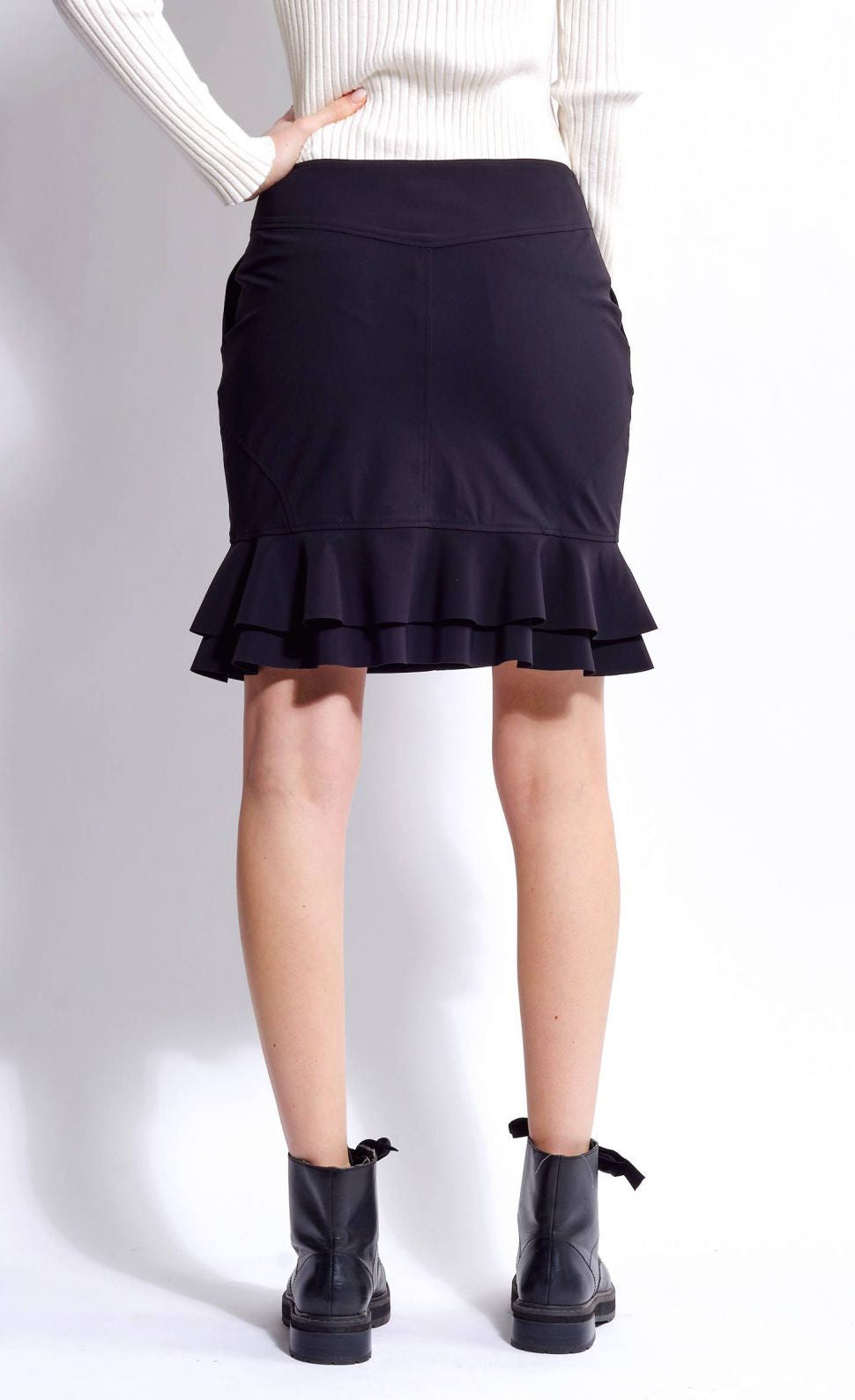 Back view of the bottom half of a woman wearing the mid-length indies cosmic black trumpet skirt with ruffles at the bottom.
