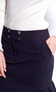A close up front left-sided view of a woman wearing a black indies cosmic trumpet skirt with her hand in the side pocket and a view of the front zipper with a two-button closure.