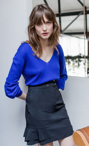 Front view of woman wearing a blue top and a mid-length black indies cosmic skirt with side ruffles at the bottom.