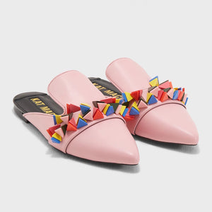 Front view of a pair of the kat maconie issa mule. This slip on mule is pink with multicolored tiny pyramid shaped decorations on the upper. The shoe has a pointed toe.