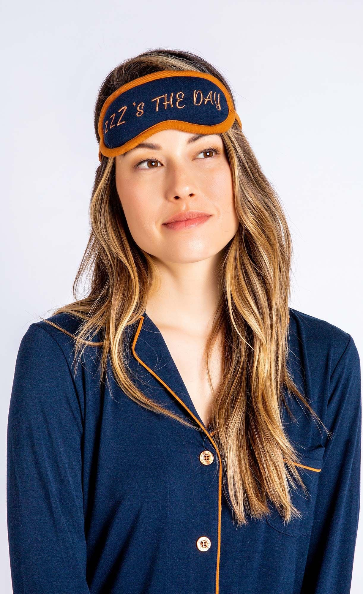 Close up of woman wearing navy pj top and sleep mask that say's Z's the day from PJ Salvage