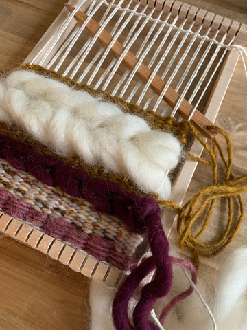 A wood tapestry needle is woven through a small hand loom along with yarns of mauve and gold, and a white braid of roving.