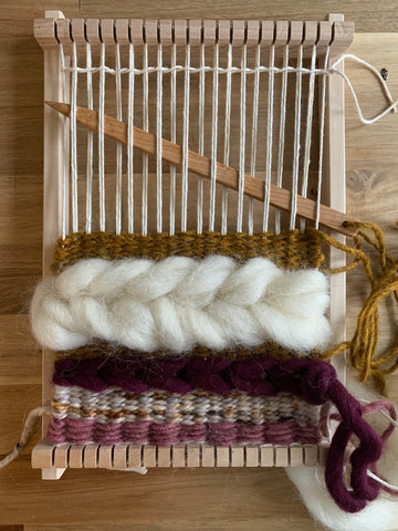 A small hand loom rests on a table with woven colors of mauve and gold, and a large white braid made of roving.