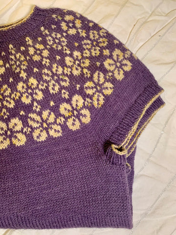 A purple short sleeved wool sweater sits folded. It has a knit yoke of flowers in a white yarn speckled with yellow and green.