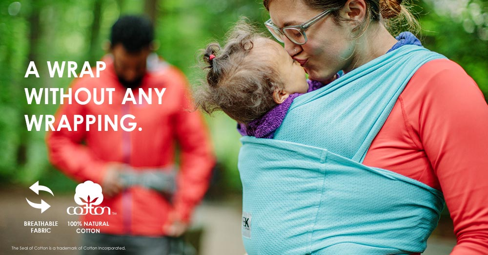 mom wearing baby in breeze carrier and kissing baby's head