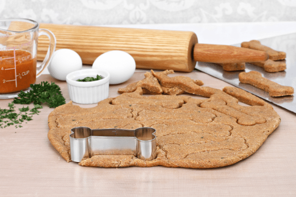 Making homemade healthy pumpkin dog biscuits with rolling pin and dough