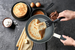 grey ceramic frying pan with a crepe being lifted off with a spatula